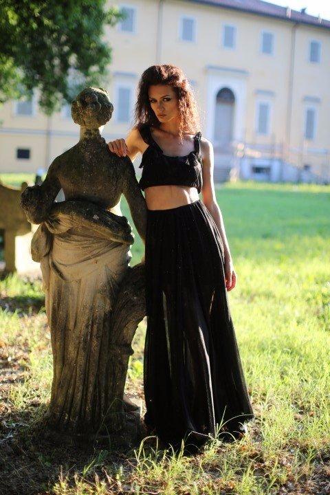 Modella con vestito nero trasparente accanto a stauta in pietra