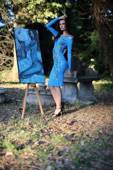 Modella con abito azzurro e fregi floreali