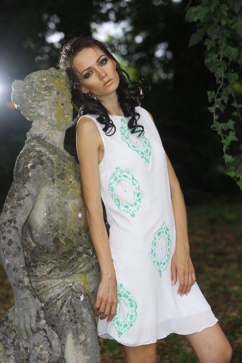 Modella con abito bianco corto a disegni verdi