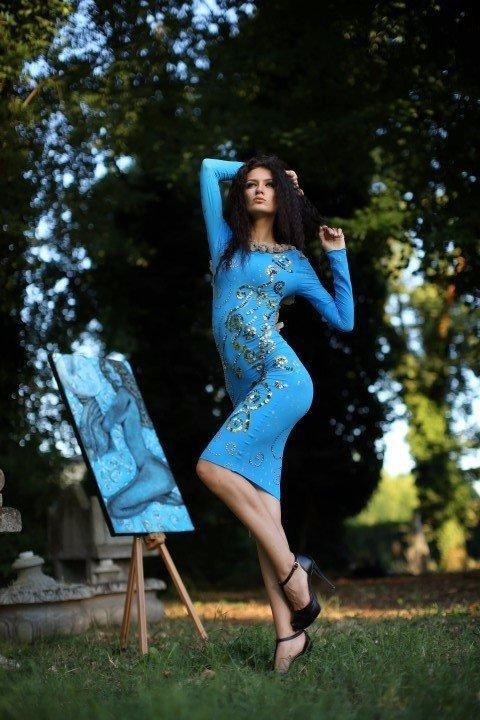 Modella con abito azzurro in posa accanto al suo ritratto