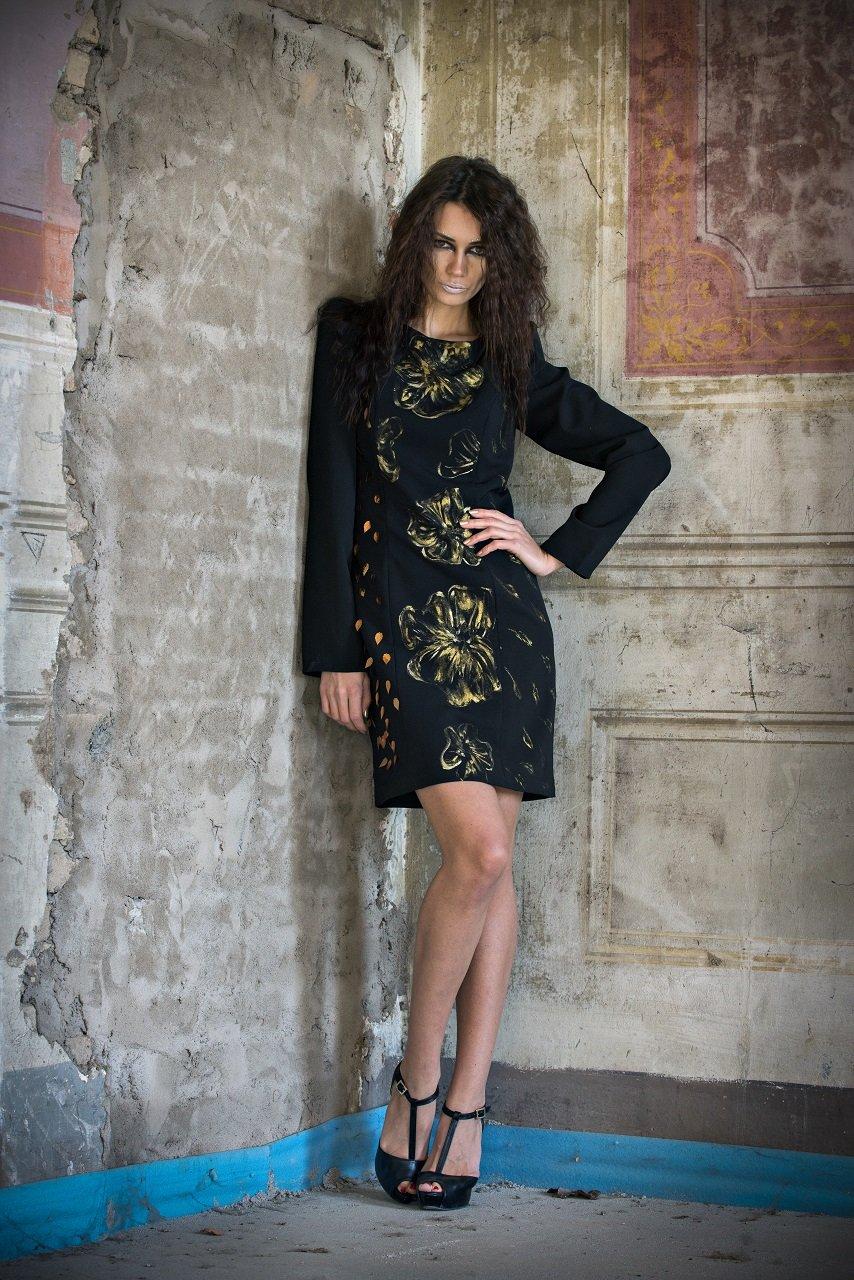 Modella con abito nero con stampe oro