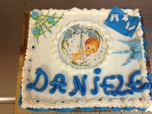 una torta di battesimo con un'immagine di un bambino sull'amaca
