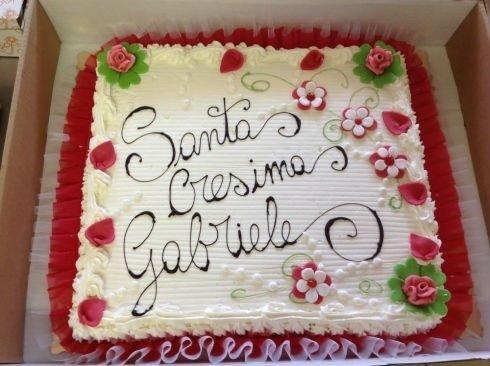 una torta da cresima con dei fiorellini e dei petali rosa