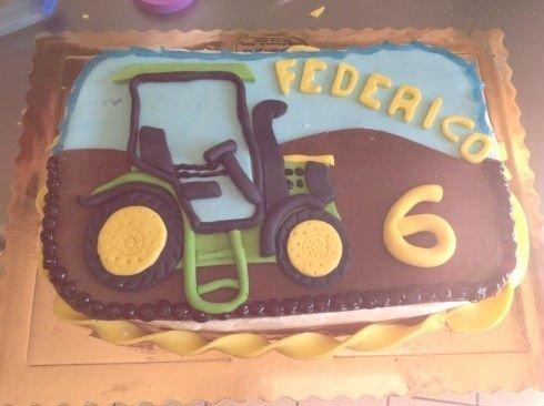 una torta con un disegno di un trattore in un terreno e il cielo azzurro
