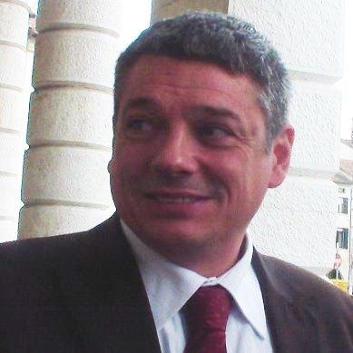 Un uomo con un completo nero mentre sorride