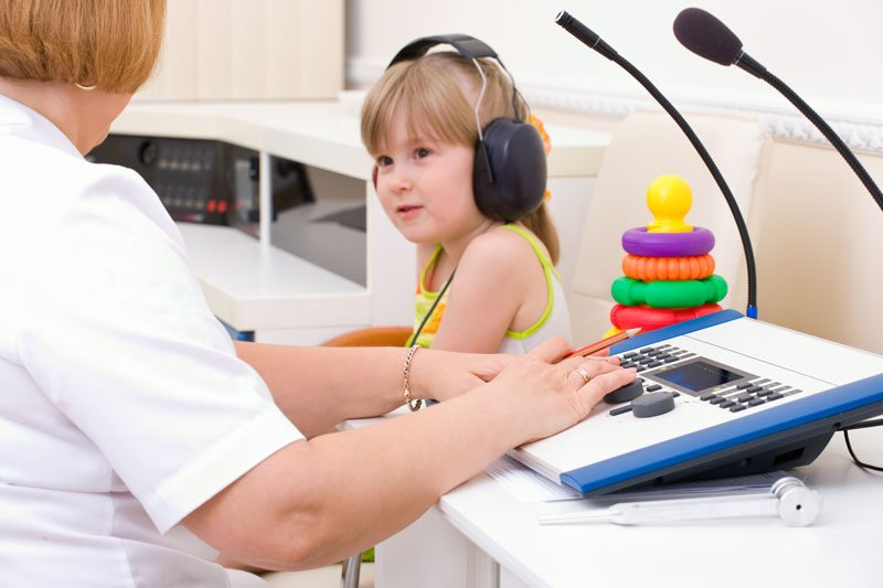 Una bambina con delle cuffie e una donna in un camice bianco seduta davanti un apparecchio con microfoni