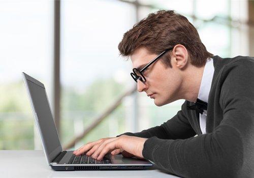 uomo che lavora al computer con degli occhiali da vista adosso