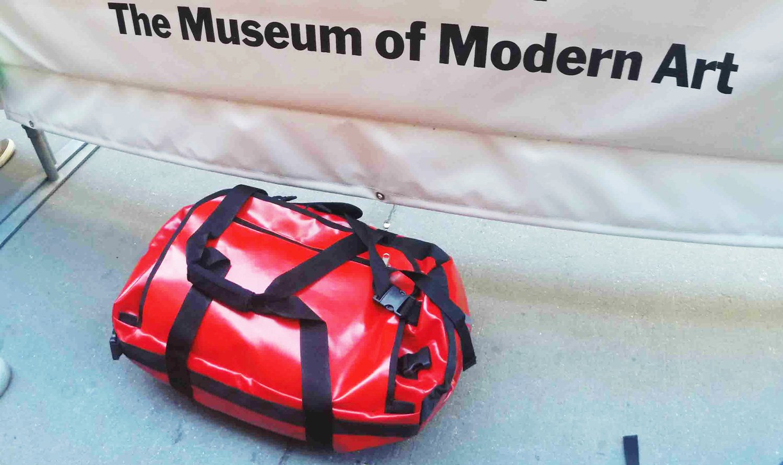 borsone rosso d'emergenza vicino a manifesto del moma museum