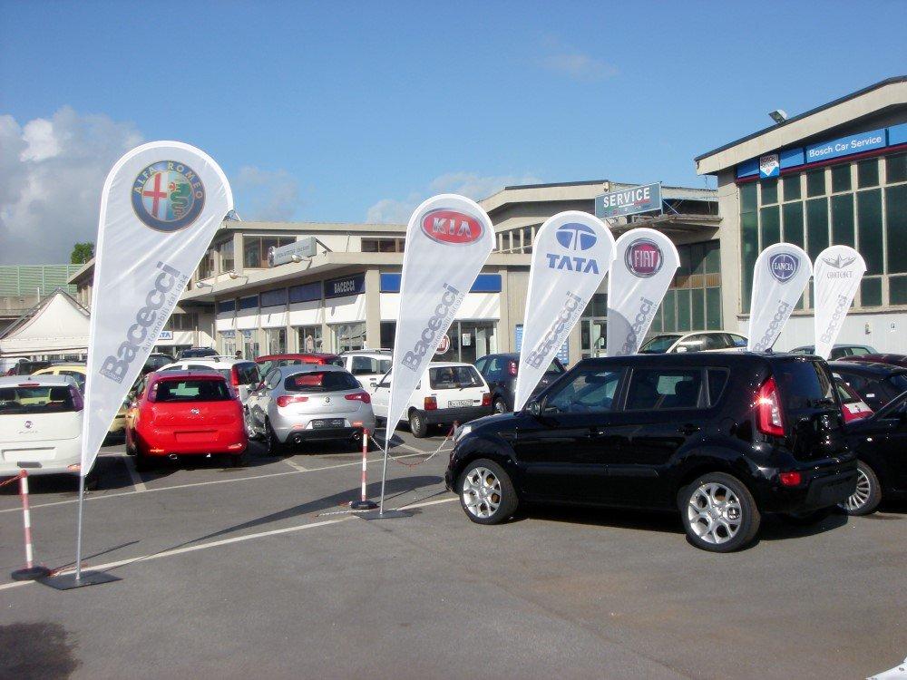 parcheggio auto con bandiere a goccia con loghi di case automobilistiche