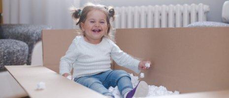 a small girl sitting inside the carton box
