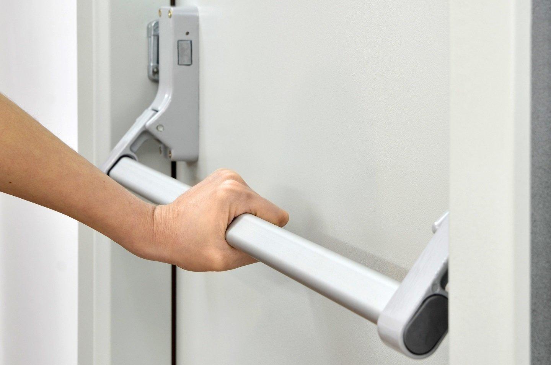 mano che spinge su una maniglia antipanico