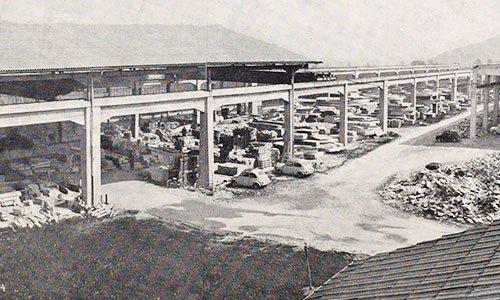 un'immagine in bianco e nero vista da lontano di un cantiere con del materiale e due macchine parcheggiate