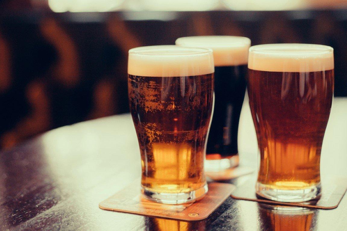 tre birre sopra un tavolo con sottobicchieri