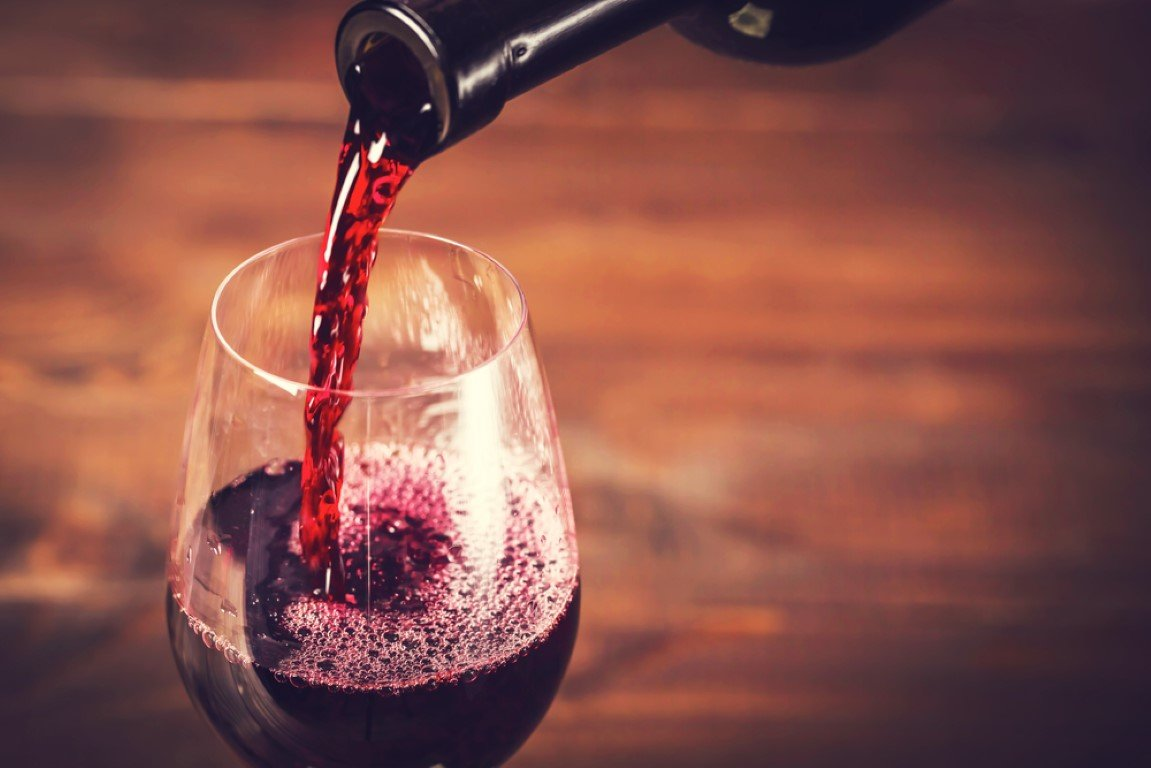 bottiglia di vino che sta versando vino in un bicchiere