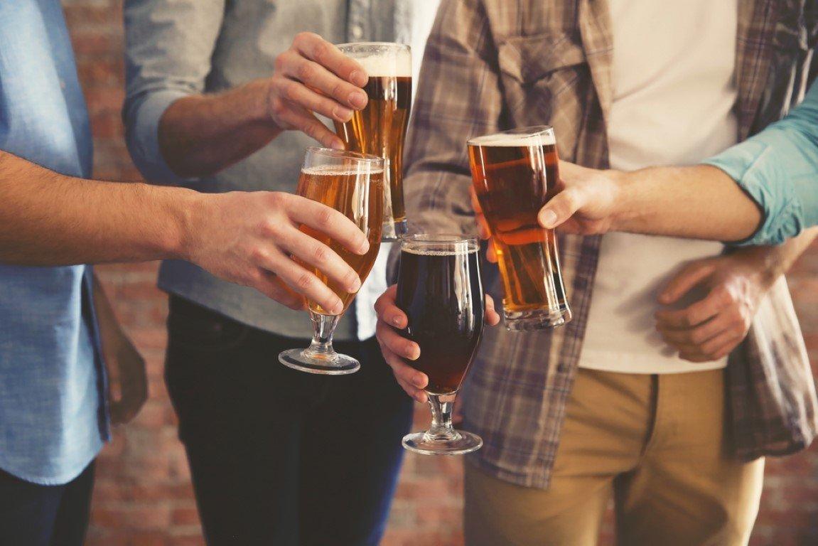 Persone che fanno un brindisi con dei boccali di birra