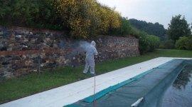 Operaio disinfetta un giardino con piscina