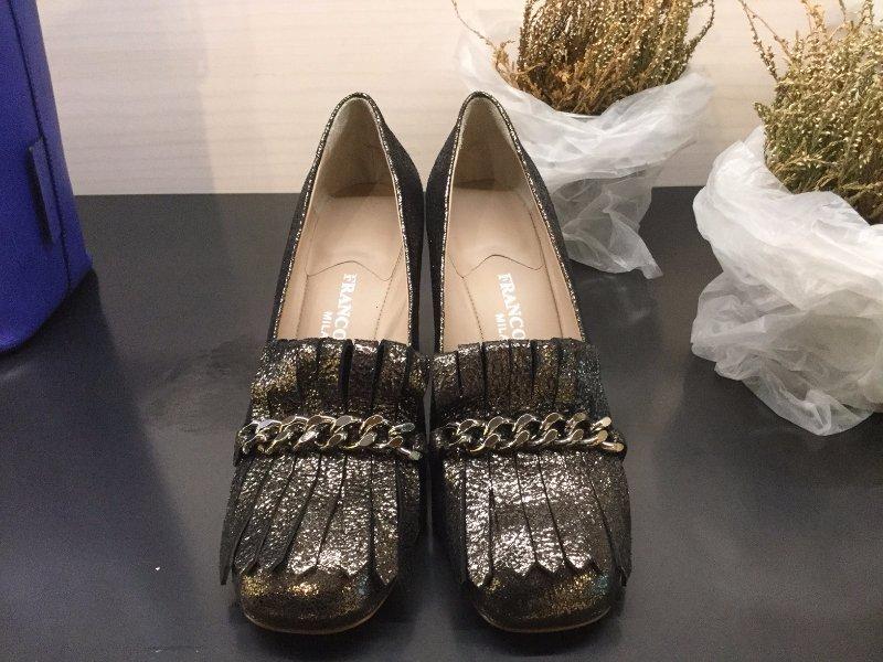 Un paio di scarpe classiche con brillantini vicino a due piantine