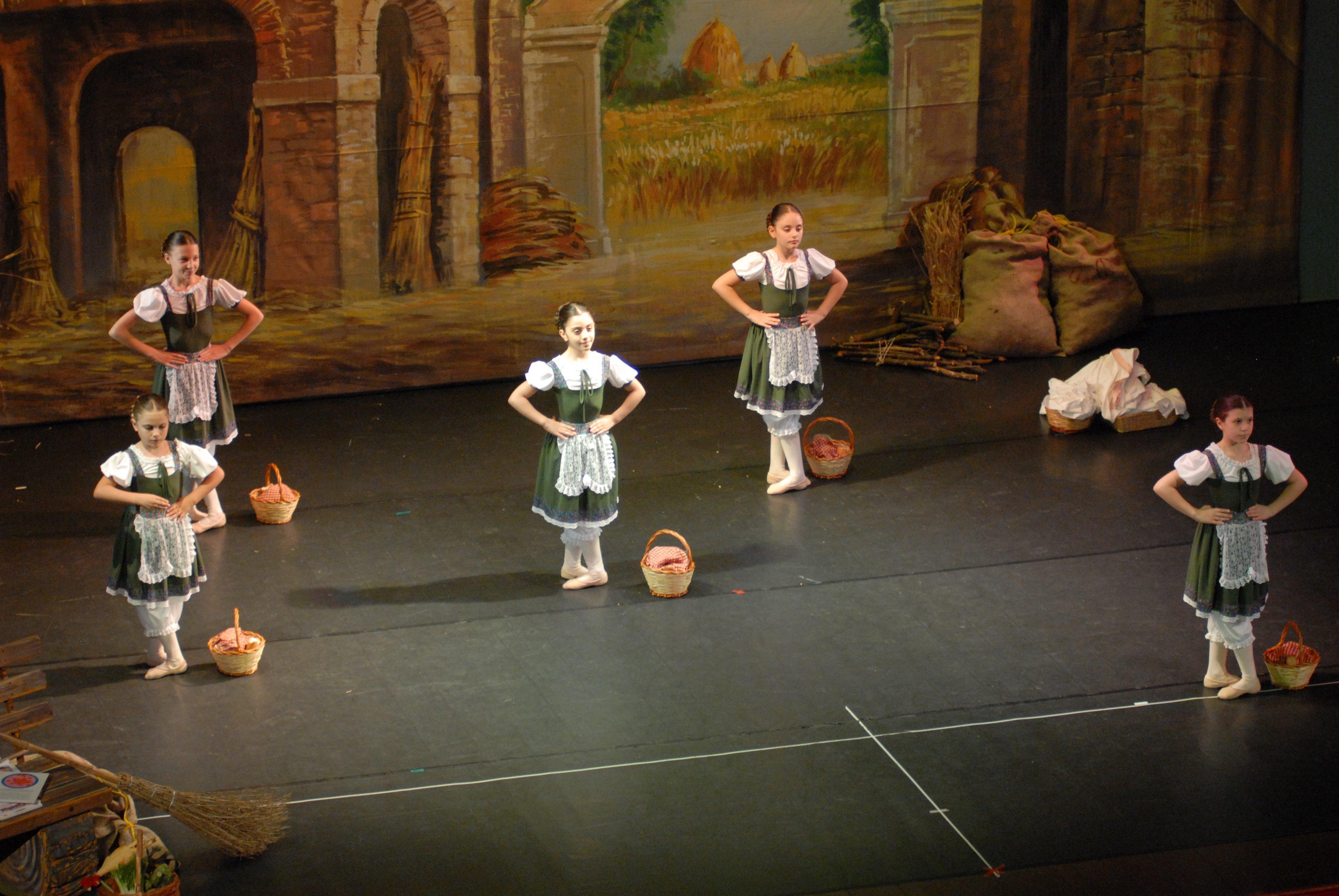 delle bambine durante uno spettacolo vestite da contadine con dei cestini di paglia accanto