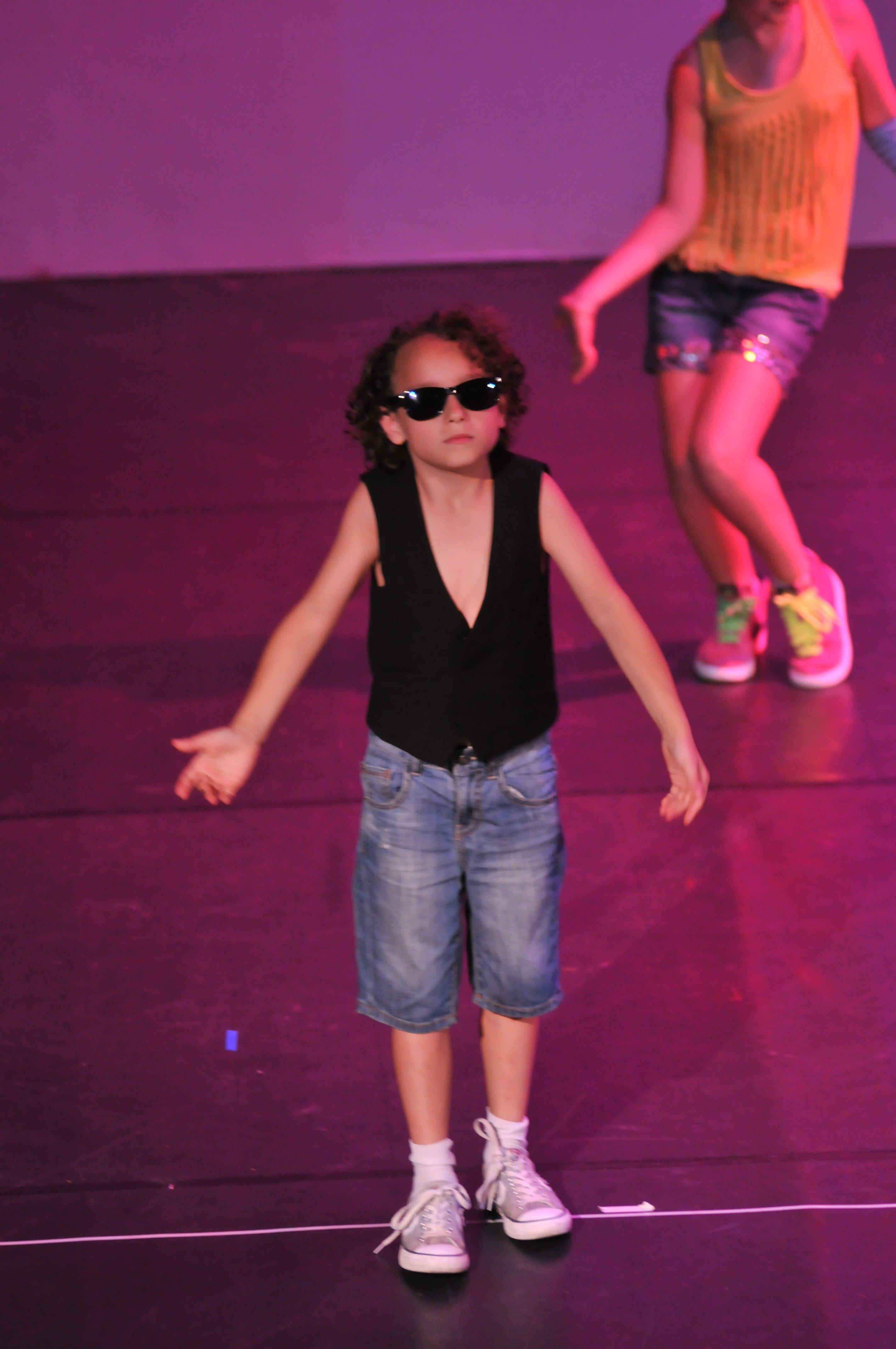 un bambino con capelli ricci, occhiali da sole e un gilet nero
