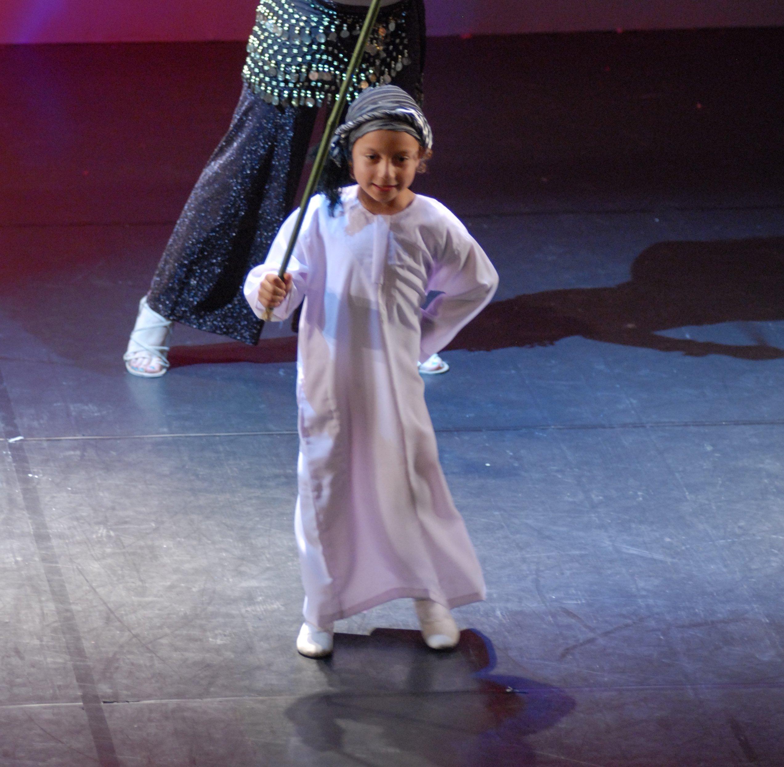 una bambina con una specie di turbante, un vestito bianco e un bastone in mano