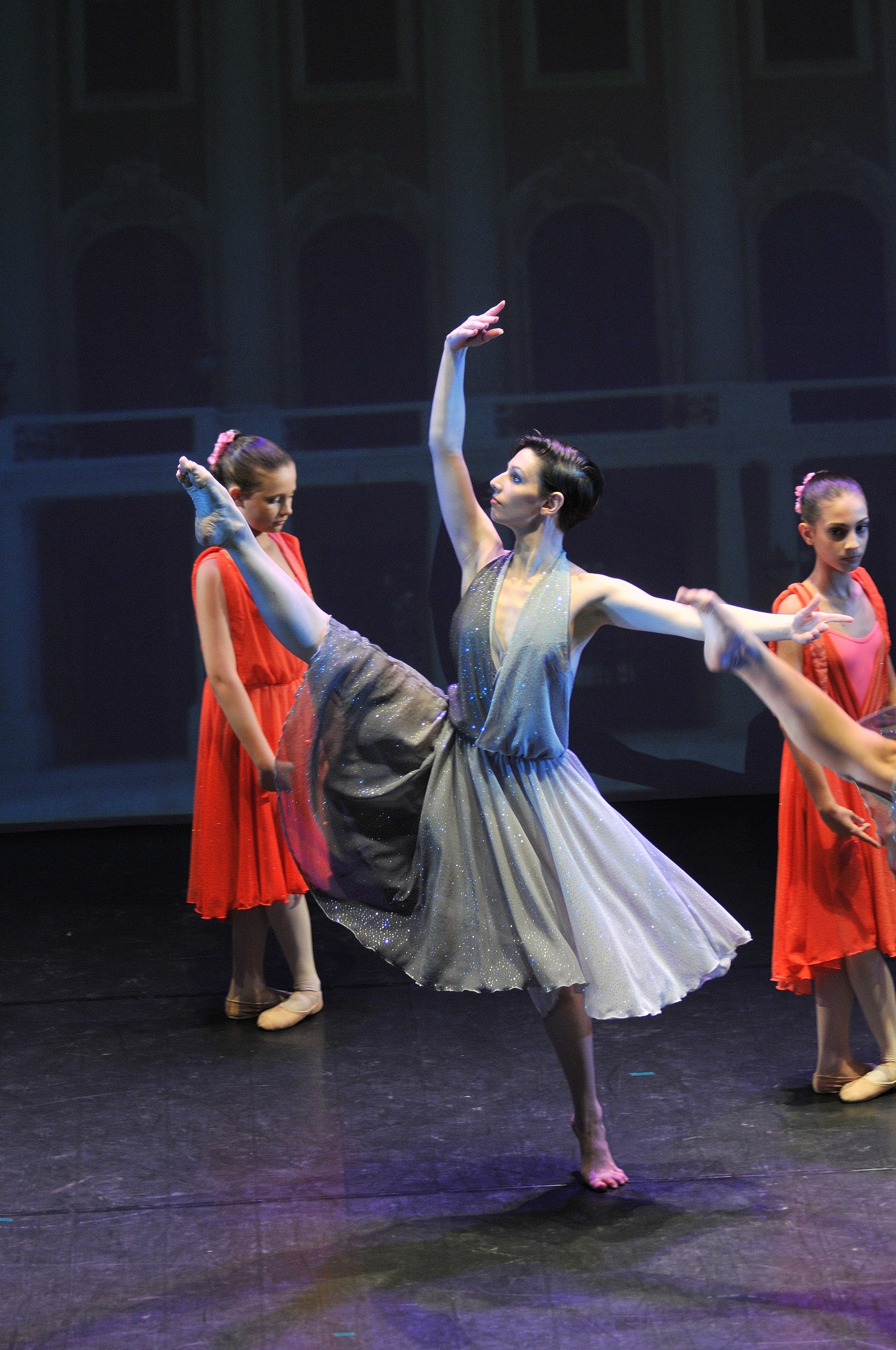 una ragazza che danza con una gamba alzata e delle bambine vestite di rosso