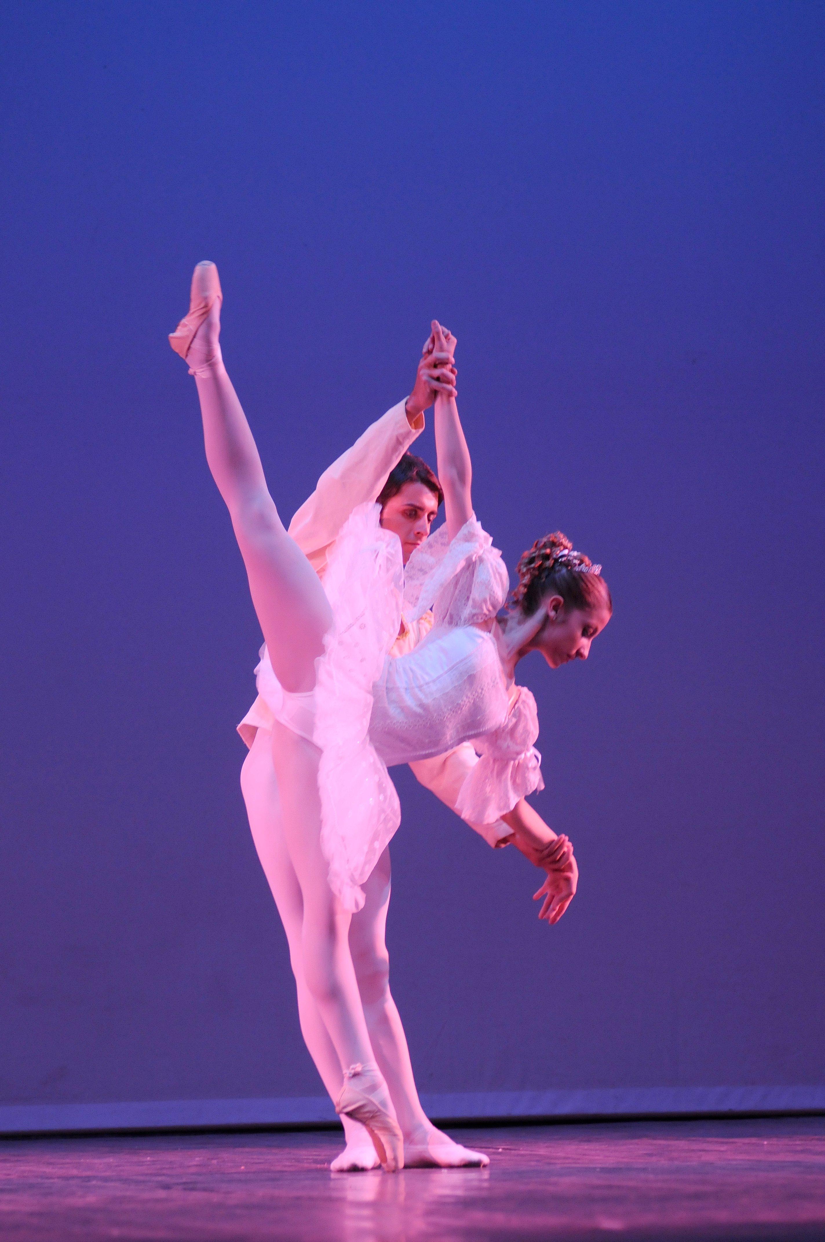 una coppia di ballerini vestiti di bianco mentre danzano