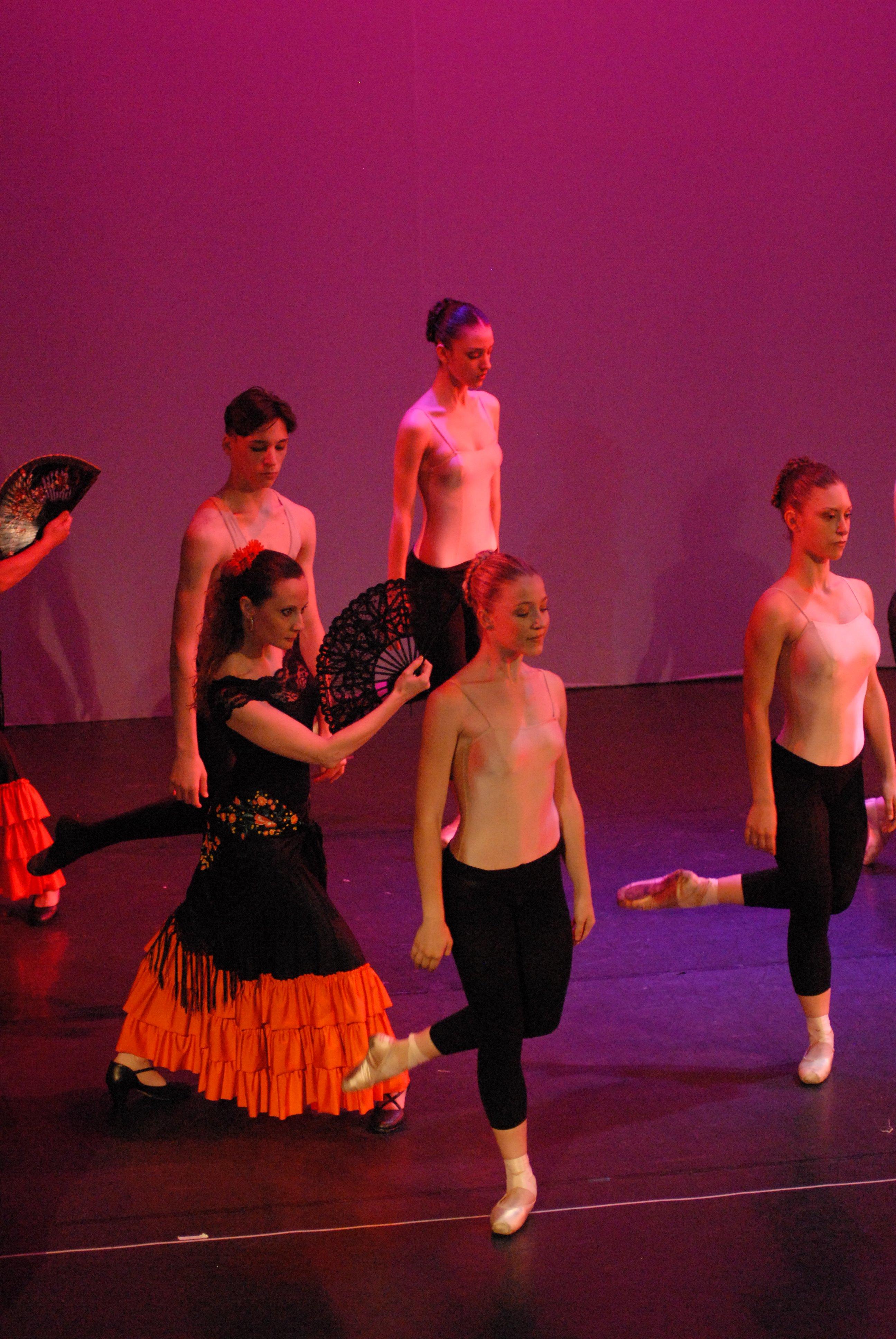 delle ragazze e un ragazzo in posa di danza e una donna vestita di nero con un ventaglio