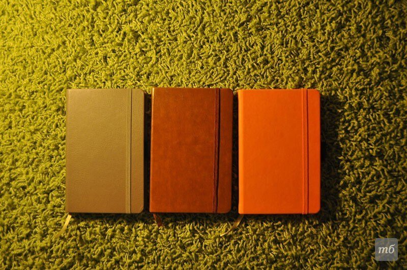 tre agende colorate su un tappeto verde