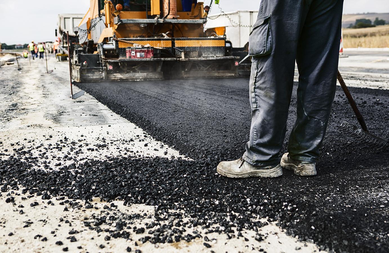 Man raking newly paved road