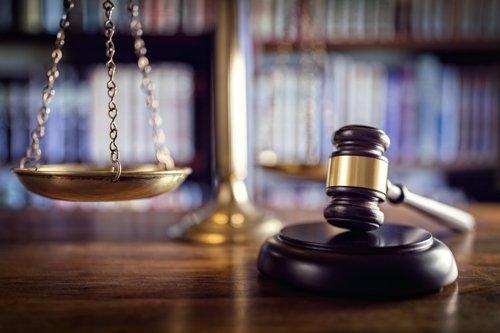 studio legale con martello e bilancia della giustizia su un tavolo