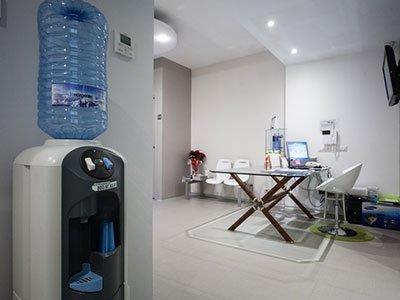 un  dispenser di acqua e un tavolo con una sedia