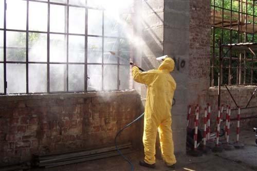 Uomo in tuta protettiva con una lancia sanifica una griglia arrugginita di una finestra