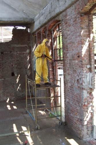 Operaio in tuta protettiva sanifica un vecchio stabile con una lancia