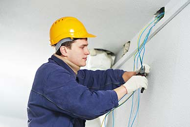 Electrician at work laying wiring cable