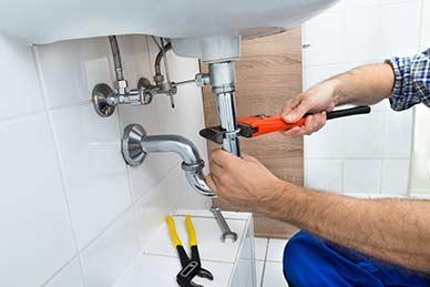 Plumber fixing sink In bathroom