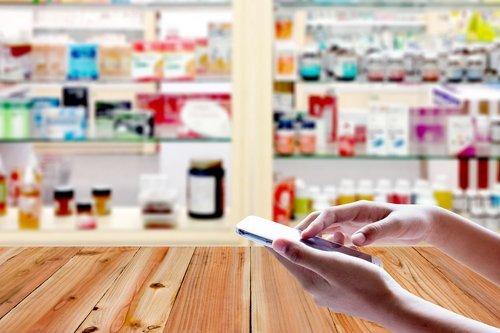 mani di una ragazza mentre usa cellulare su sfondo sfocatura della farmacia