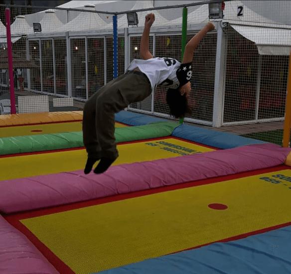bambino mentre salta su tappeti elastici