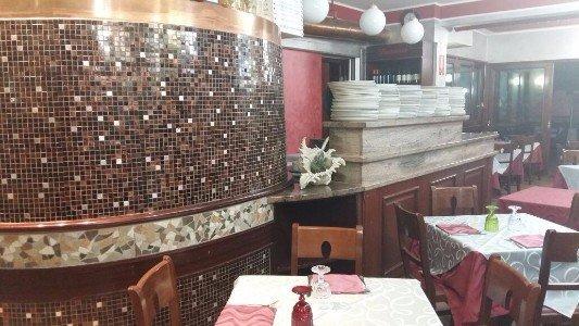 interno di un ristorante con un muro con piastrelle a mosaico e vista dei tavoli