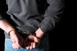 man's hands cuffed behind his back