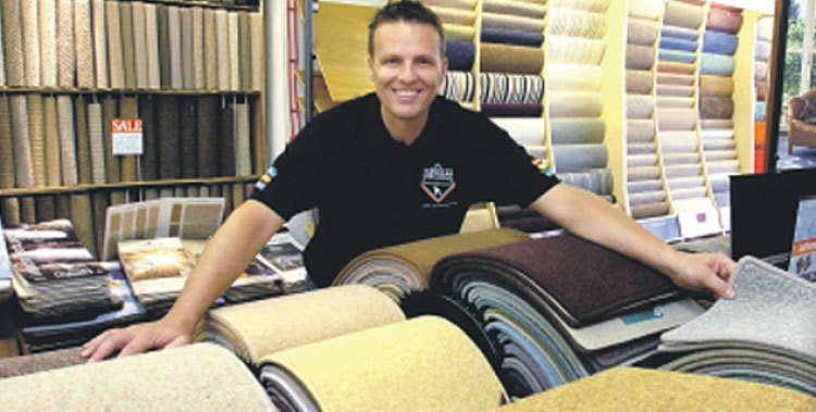happy slaesman with a selection of carpet samples