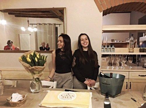 due ragazze in piedi davanti a una torta con scritto a casa mia