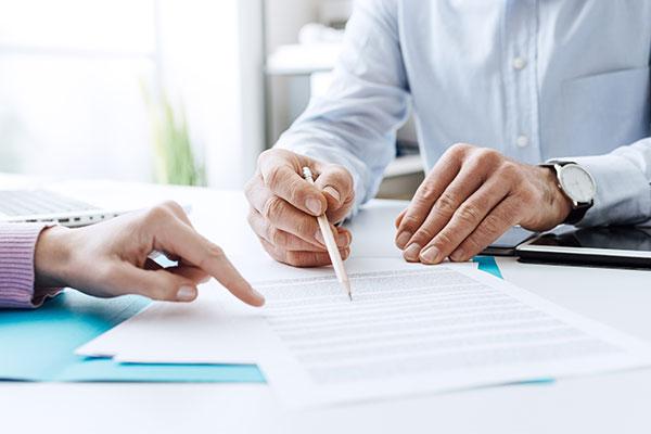 un uomo alla scrivania che scrive su un foglio e un altra persona che con il dito indice indica il foglio