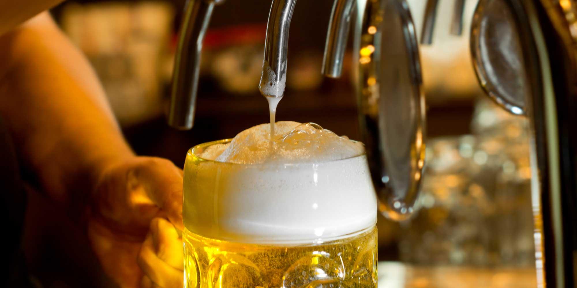 La birra sta sgorgando dalla macchina nel bicchiere da birra a Messina