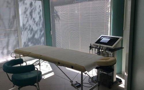 un lettino, una sedia e un macchinario odontoiatrico