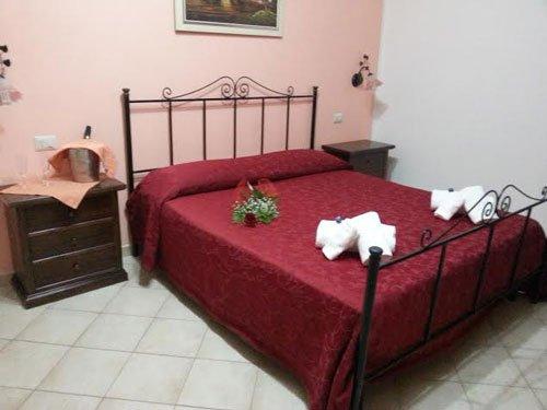 Camera Rosa e bianca con letto in tono rosso granato con asciugamani piegati e dettaglio di fiori in camera