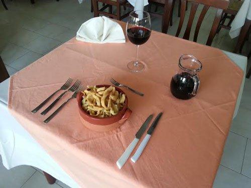 Tavola preparata con un piatto di calamari ricoperti,un bicchiere di vino rosso e la bottiglia