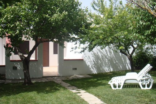 Angolo del giardino con una sedia a sdraio per riposare sotto gli alberi