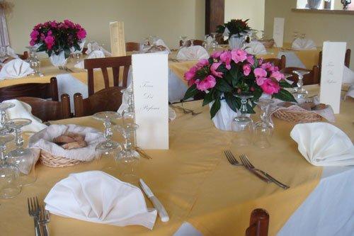 Tavolo d apranzo apparecchiato con tovaglioli, posate, menù e centrotavola con fiori