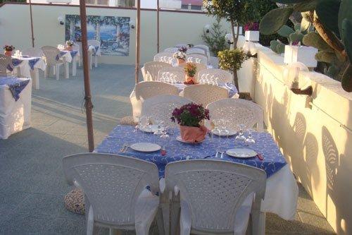 Tavoli disposti in terrazza con tonalità blu