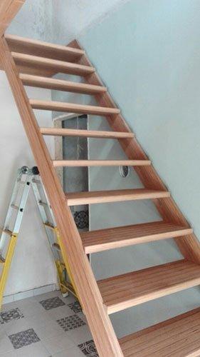 delle scale in legno e accanto una scala  in metallo